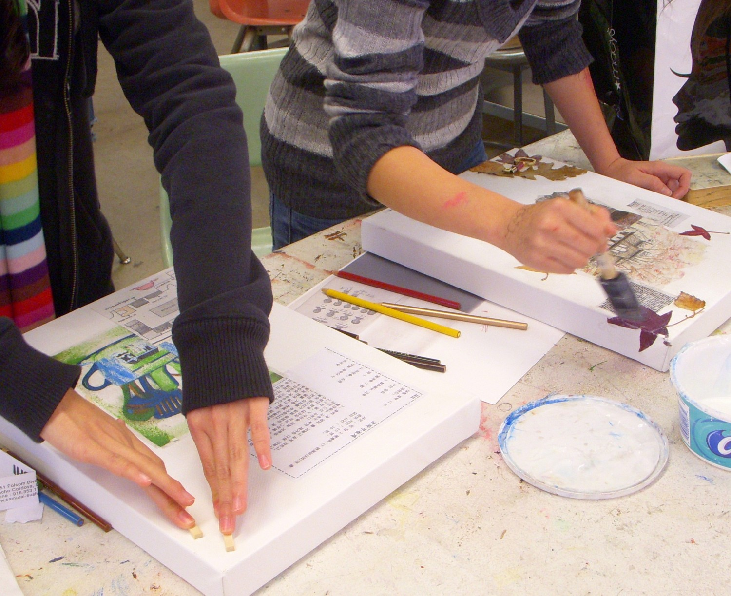 students in a high school art class working on mixed media artworks